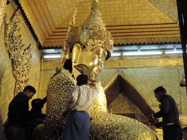Gold leaf being applied to the Buddha by men only