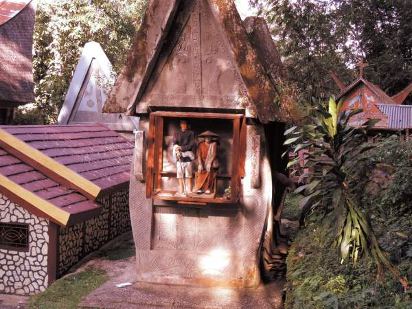 A tomb in the shape of a Tongkonan and tau tau